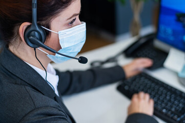Close-up of a female receptionist wearing a facial mask talking on a headset while sitting at a work desk in the office. Portrait of a manager working during a coronavirus epidemic.