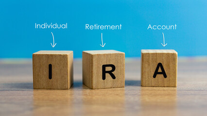 IRA individual retirement account word on wood cube block with blue background