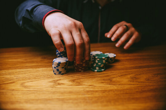 casino, gambling, poker, people and entertainment concept - close up of poker player with chips at casino table. Gambler man hands pushing large stack of colored poker chips across gaming table.