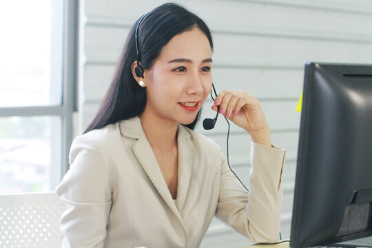 Businesswoman Call Center and technical Support staff with headset Smiling and talking in work. Asian customer support team.