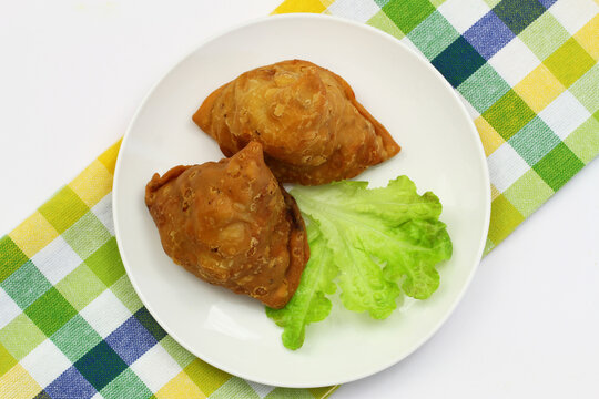 Two Indian samosas on green lettuce on white plate on checkered cloth