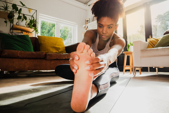 Young female working out from home and stretching legs on yoga mat