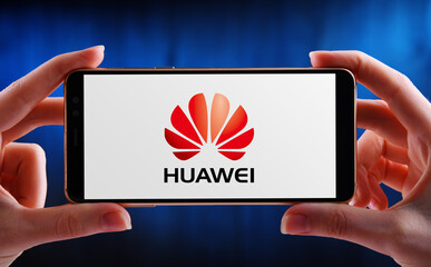 Hands holding smartphone displaying logo of Huawei