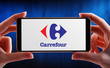 Hands holding smartphone displaying logo of Carrefour