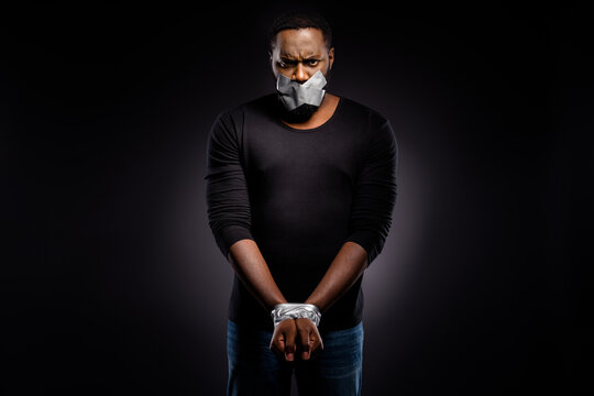 Photo of mad afro american guy arrested police adhesive taped hands mouth cover close taboo speaking talking racism isolated over black color background