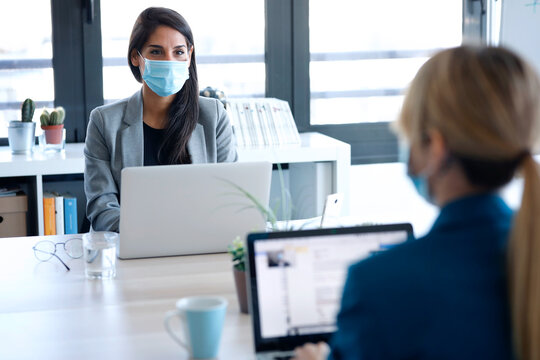 Two business women wearing a hygienic face mask while work with laptops in the coworking space. Social distancing concept.