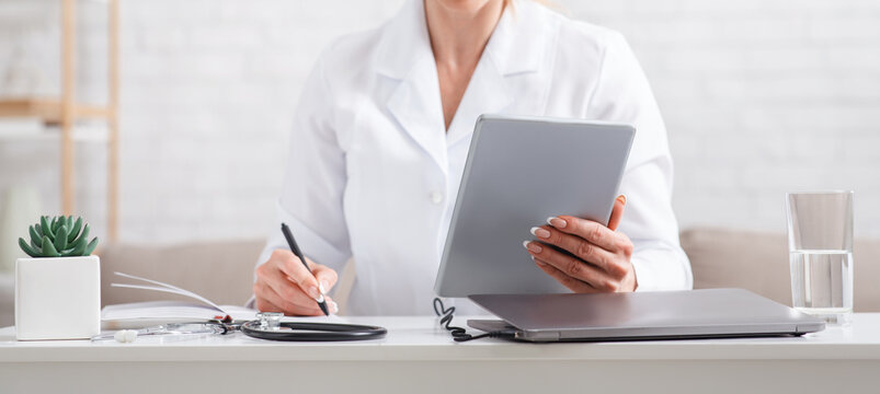Modern online record to visit to doctor. Woman in uniform with tablet in hands