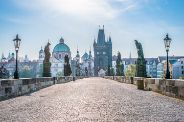 Medieval stone Charles bridge with statues of saints in a thin haze during sunrise, Prague, Czech Republic