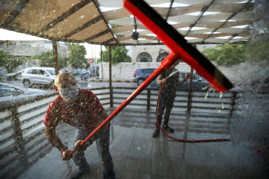 A worker cleans a window of a cafe before reopening to the public for the first time since the start of the coronavirus disease (COVID-19) restrictions in Amman