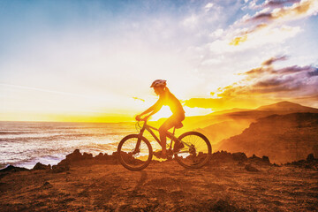 MTB mountain biking cyclist woman rider riding bike on summer coastal trail sunset landscape. Girl silhouette of athlete doing cycle sports outdoor. Healthy and Active lifestyle.