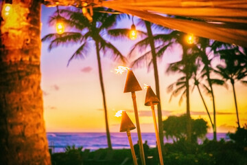 Hawaii luau party with fire torches at sunset. Hawaiian icon, lights burning at dusk at Waikiki beach resort restaurant for outdoor lighting cozy atmosphere.