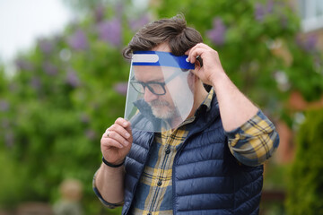 Man putting on face shield on street of city or park. Safety during COVID-19 outbreak. Lifting virus lockdown. Social distancing and face mask - security measures when exiting quarantine