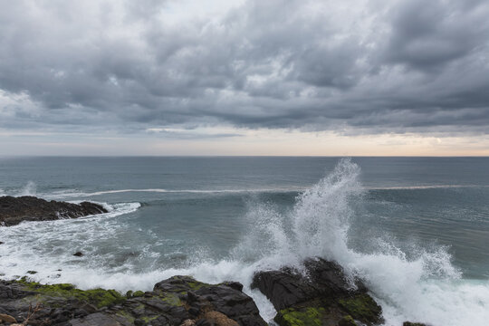 storm clouds above the ocean while waves crashing on the rocky beach