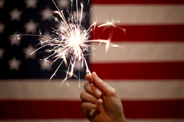 Photo sur Aluminium Inde Hand holding lit sparkler in front of the American Flag for 4th of July celebration