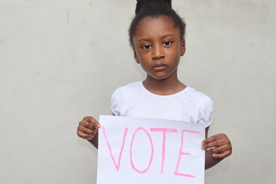 Girl holding white paper sign with the word Vote written in pink letters