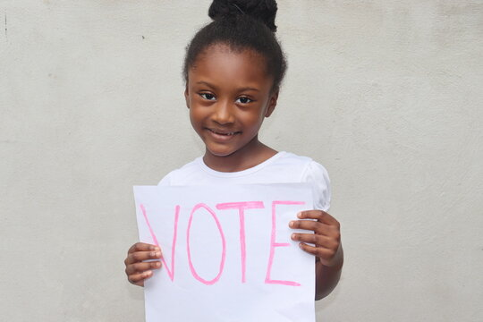 African American child holding white paper sign with word Vote in pink letters standing outdoors