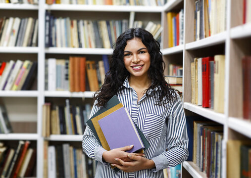 Smiling latina girl holding textbooks at library