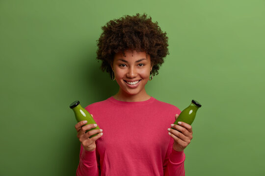Portrait of happy smiling dark skinned woman has healthy natural lifestyle, holds two bottles of green vegetable smoothie, has proper nutrition, enjoys weight loss drink, wears rosy jumper, smiles