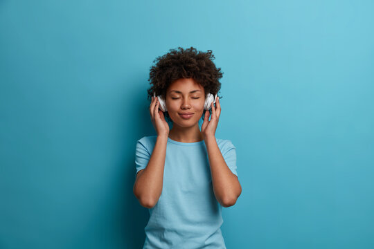 Satisfied curly young Afro American woman has carefree happy mood, closes eyes and listens music in headphones, wears casual blue t shirt, poses indoor. People, leisue, entertainment concept