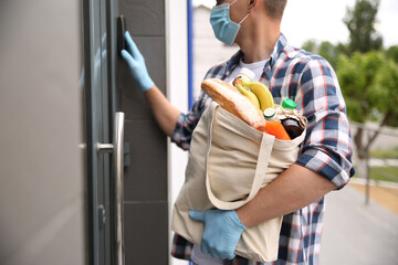 Male volunteer with products ringing doorbell outdoors. Aid during coronavirus quarantine