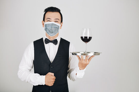 Portrait of happy restaurant waiter in medical mask serving glass of red wine
