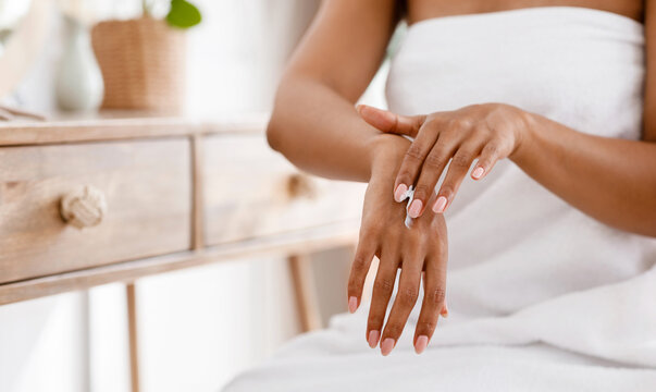 Skin nutrition concept. Unrecognizable black woman applying moisturizing cream to her hands