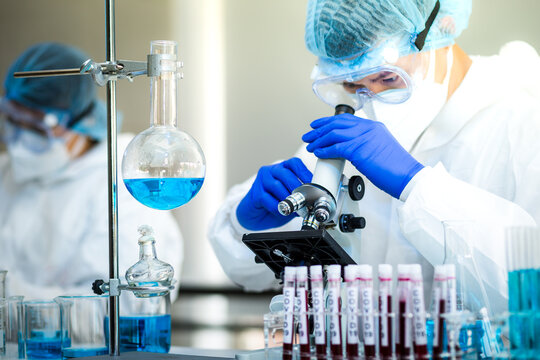 Scientist or researcher hand in blue gloves holding flu, measles, coronavirus, covid-19 vaccine disease preparing for human clinical trials vaccination shot, medicine and drug concept.