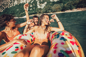 Young trendy people having fun swimming in summer vacation, relaxing on inflatable ring.