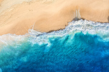 Beach and waves as a background from top view. Blue water background from drone. Summer seascape from air. Bali island, Indonesia. Travel image