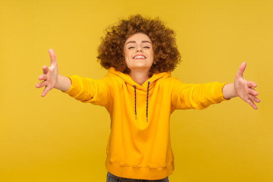Come into my arms! Portrait of extremely happy, friendly curly-haired woman in urban style hoodie outstretching hands to embrace, giving free hugs and welcoming. indoor studio shot, yellow background
