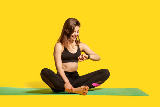 Happy sporty girl in tight sportswear sitting on gym mat, looking time, checking pulse in fitness tracker, using smartwatch to monitor heart beat, wearable app. Healthy lifestyle, isolated studio shot