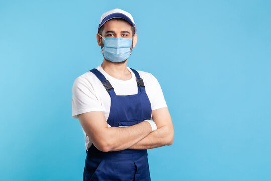 Portrait of happy handyman in overalls mask, and cap standing with crossed hands, profession of service industry, courier delivery. Expert house repairman in workwear smiling. indoor shot isolated
