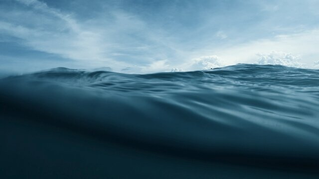 Wave on moving water surface close up in the middle of the screen.  Under Water Surface in the middle of the sea