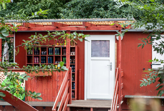 tiny wooden house in a german kindergarden, white door and shelf with rubber boots