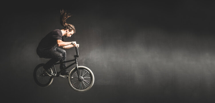 Young man jumping on BMX bicycle