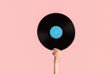 Girl hand showing retro vinyl gramophone record on pink background, closeup