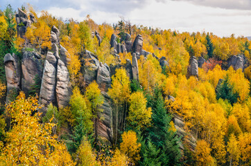 Tall rock formations  pointing out of the colorful autumn forest, Czech Republic