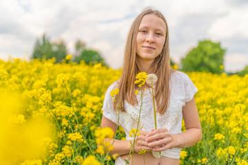 junges kaukasisches Mädchen posiert in der Natur im sommerlichen, gelben Rapsfeld