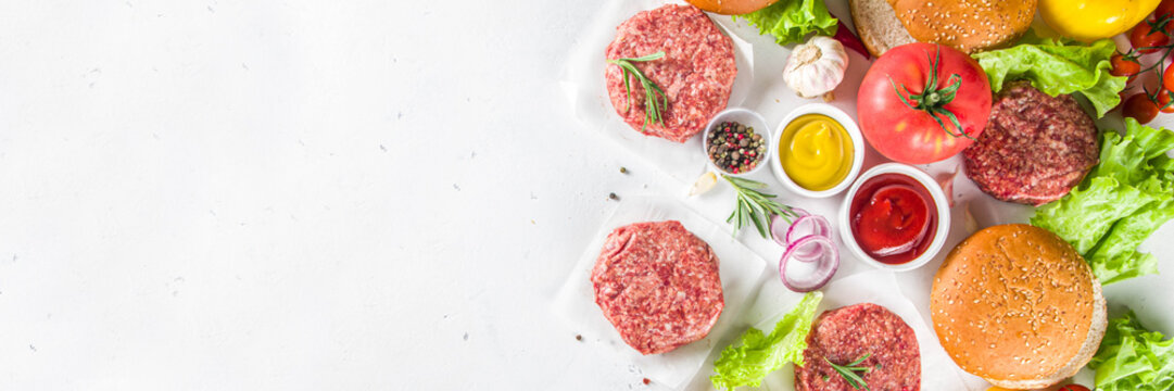 Cooking burger background. Set various cheeseburger  and beefburger ingredients - bun, tomatoes, onion, lettuce, sauces, cheese and raw burger cutlets, ready for barbecue grill. Burger bbq party fest