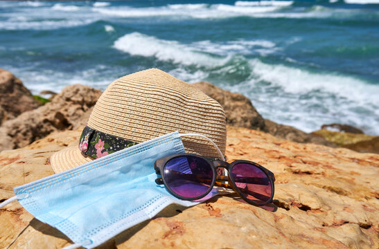Women's accessories with a fedora straw hat and sunglasses and a face mask protection from coronavirus COVID-19 on a rock by the ocean on a hot summer day, rocky beach in Tel-Aviv Israel