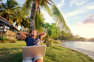 Work and vacation. Young man working on laptop computer on the tropical beach under the palm tree. Wall mural
