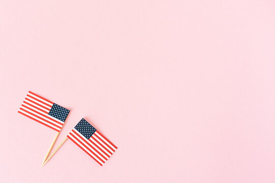 Two american flag on pink background, flat lay. 4th of july, usa independence day. Celebration in America. Copy space for text.
