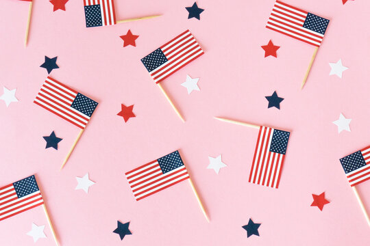 Many little american flags and stars on pink background, flat lay. 4th of july, happy usa independence day. Celebration in America, good mood.