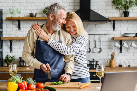 Beautiful mature couple hugging while cooking vegetable salad at kitchen table
