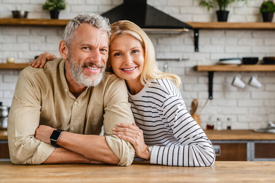 Portrait of middle aged couple hugging while standing together in kitchen at home