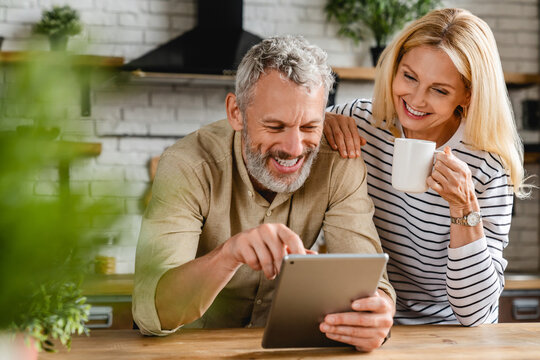 Happy senior couple using digital tablet in kitchen at home