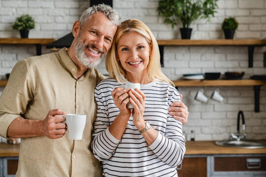 Beautiful middle aged couple drinking tea or coffee at home while looking at camera