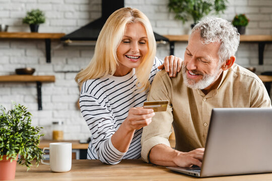 Middle aged smiling couple doing some online shopping at home