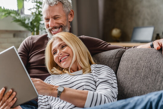 Close up of smiling middle aged couple using digital tablet on couch at home interior