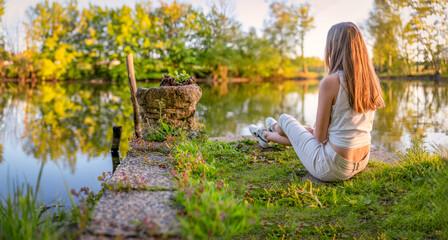 junges, kaukasisches Mädchen posiert in der Natur im lichtdurchfluteten Abendlicht.